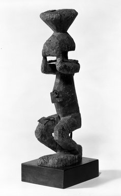Dogon. <em>Figure with Legs Bent</em>, late 19th or early 20th century. Wood, iron, metal, 11 3/4 x 3 x 4 1/4 in. (29.8 x 7.6 x 10.8 cm). Brooklyn Museum, Gift of Gaston T. de Havenon, 73.179.5. Creative Commons-BY (Photo: Brooklyn Museum, 73.179.5_bw.jpg)