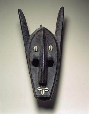 Bamana. <em>Hyena Mask, Kor'e Society (Souroukou)</em>, late 19th-early 20th century. Dark wood, cowrie shells, oil, accumulated materials, 17 1/2 x 6 7/8 x 7 in. (44.5 x 17.5 x 17.8 cm). Brooklyn Museum, Gift of Mr. and Mrs. Gordon Douglas, 74.211.7. Creative Commons-BY (Photo: Brooklyn Museum, 74.211.7_view2_SL4.jpg)