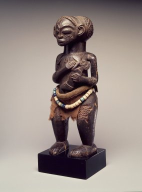 Attributed to Satshombo. <em>Female Figure with Child</em>, late 19th or early 20th century. Wood, fiber, plastic, 10 3/4 x 4 x 3 1/4in. (27.3 x 10.2 x 8.3cm). Brooklyn Museum, Gift of Marcia and John Friede, 74.66.4. Creative Commons-BY (Photo: Brooklyn Museum, 74.66.4.jpg)