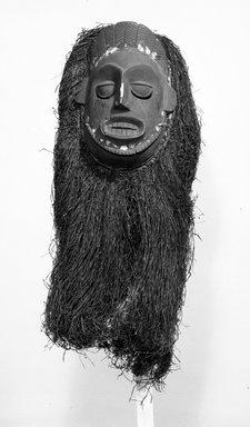 Ibibio. <em>Ekpo Society Mask with Fringe Attachment</em>, early 20th century. Wood, raffia or palm fiber, organic material, cloth fiber, 29 x 15 x 8 in. (73.7 x 38.1 x 20.4 cm). Brooklyn Museum, Gift of Mr. and Mrs. J. Gordon Douglas III, 75.189.7. Creative Commons-BY (Photo: Brooklyn Museum, 75.189.7_bw.jpg)