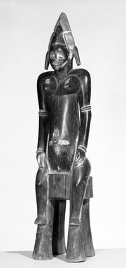 Senufo. <em>Seated Female Figure (Tugubele)</em>, early 20th century. Wood, pigment, 34 1/2 x 8 1/4 x 6 3/4 in. (87.6 x 21.0 x 17.1 cm). Brooklyn Museum, Gift of Mr. and Mrs. Milton F. Rosenthal, 76.167.1. Creative Commons-BY (Photo: Brooklyn Museum, 76.167.1_bw.jpg)