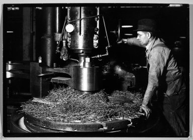 Lewis Wickes Hine (American, 1874-1940). <em>[Untitled] (Man in Hat Standing at Machine)</em>, 1936-1937. Gelatin silver photograph, 4 3/4 x 7 1/4 in.  (12.1 x 18.4 cm). Brooklyn Museum, Gift of the National Archives, 79.143.142 (Photo: Brooklyn Museum, 79.143.142_bw.jpg)