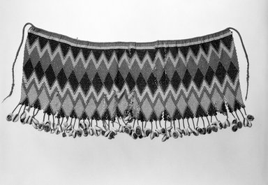 Kirdi (ie. Gisinga, Motu, Gude, Glidder, Fali). <em>Cache Sex/Apron</em>, late 19th or early 20th century. Fiber, glass beads, cowrie shells, metal, 21 3/8 x 9 1/2 in. (54.3 x 24.1 cm). Brooklyn Museum, Gift of Jay M. Haft, 80.243.1. Creative Commons-BY (Photo: Brooklyn Museum, 80.243.1_bw.jpg)