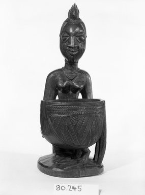 Yorùbá. <em>Kneeling Female Figure Holding a Bowl (Agere Ifa)</em>, late 19th or early 20th century. Wood, applied materials, (metal & beads in bag), h: 11 3/3 in. (30.0 cm). Brooklyn Museum, Gift of Ann W. Walzer, 80.245. Creative Commons-BY (Photo: Brooklyn Museum, 80.245_front_bw.jpg)