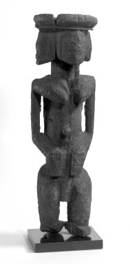 Dogon. <em>Figure with Four Faces (Ginin)</em>, late 19th or early 20th century. Wood, iron, sacrificial materials, 14 1/4 in. (32.6 cm). Brooklyn Museum, Gift of Avery Eliscu, 82.155. Creative Commons-BY (Photo: Brooklyn Museum, 82.155_view1_bw.jpg)