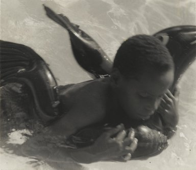 Consuelo Kanaga (American, 1894-1978). <em>[Untitled] (Boy with Rubber Dolphin)</em>. Gelatin silver photograph, 3 7/8 x 4 3/8 in. (9.8 x 11.1 cm). Brooklyn Museum, Gift of Wallace B. Putnam from the Estate of Consuelo Kanaga, 82.65.95 (Photo: Brooklyn Museum, 82.65.95_PS2.jpg)