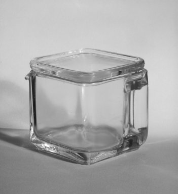 Wilhelm Wagenfeld (1900-1990). <em>Short Pitcher with Lid, from 10-Piece Set of Kitchen Storage Glassware, Kubus</em>, ca. 1942. Clear glass, overall height: 3 1/2 in. (9.0 cm). Brooklyn Museum, Gift of Barry Friedman, 84.121.3a-b. Creative Commons-BY (Photo: Brooklyn Museum, 84.121.3a-b_bw.jpg)