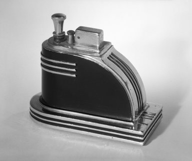 "Louis V. Aronson. <em>Cigarette Lighter, ""Ronson Touch-Tip,""</em> ca. 1935. Chrome and black-enameled metal, 3 3/8 x 4 3/8 x 2 1/4 in. (8.6 x 11.1 x 5.7 cm). Brooklyn Museum, Gift of David A. Hanks, 84.276a-b. Creative Commons-BY (Photo: Brooklyn Museum, 84.276a-b_bw.jpg)"