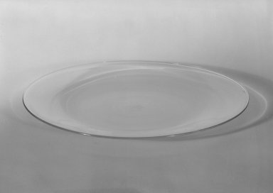 Wilhelm Wagenfeld (1900-1990). <em>Cake Plate</em>, 1930-1934. Clear heat-resistant glass, 9/16 x 7 7/8 in. (1.4 x 20 cm). Brooklyn Museum, Gift of Barry Friedman, 84.64.14. Creative Commons-BY (Photo: Brooklyn Museum, 84.64.14_bw.jpg)
