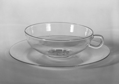 Wilhelm Wagenfeld (1900-1990). <em>Cup and Saucer</em>, 1930-1934. Clear heat-resistant glass, 1 3/8 x 5 1/8 x 3 7/8 in. (3.5 x 13 x 9.8 cm). Brooklyn Museum, Gift of Barry Friedman, 84.64.8a-b. Creative Commons-BY (Photo: Brooklyn Museum, 84.64.8_bw.jpg)