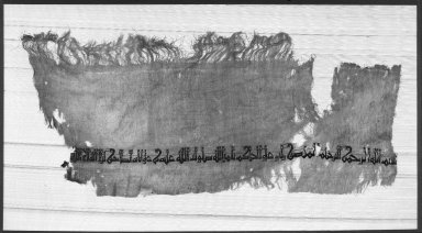 <em>Tiraz Textile Fragment</em>, 996-1021. Linen ground, silk tabby-woven inscription, 10 3/8 x 24 in. Brooklyn Museum, Gift of the Ernest Erickson Foundation, Inc., 86.227.100. Creative Commons-BY (Photo: Brooklyn Museum, 86.227.100_acetate_bw.jpg)