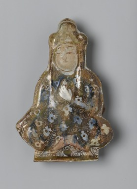 <em>Tile in the Shape of a Seated Figure</em>, early 13th century. Ceramic; fritware, molded and painted in luster and cobalt blue on an opaque white glaze, 5 1/2 x 4in. (14 x 10.2cm). Brooklyn Museum, Gift of the Ernest Erickson Foundation, Inc., 86.227.69. Creative Commons-BY (Photo: Brooklyn Museum, 86.227.69_PS2.jpg)
