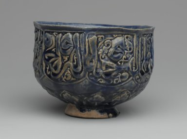 Hasan Al-Qashani. <em>Octagonal Bowl with Inscriptions</em>, late 12th century. Ceramic; fritware, with carved and molded decoration under a cobalt blue glaze, 4 5/16 x 6 3/8 in. (11 x 16.2 cm). Brooklyn Museum, Gift of the Ernest Erickson Foundation, Inc., 86.227.89. Creative Commons-BY (Photo: Brooklyn Museum, 86.227.89_side1_PS2.jpg)