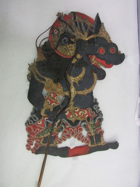 <em>Shadow Play Figure (Wayang kulit)</em>, before 1893. Leather, pigment, wood, fiber, metal, 22 1/4 × 11 7/16 in. (56.5 × 29 cm). Brooklyn Museum, Brooklyn Museum Collection, 00.167. Creative Commons-BY (Photo: , CUR.00.167_overall.jpg)