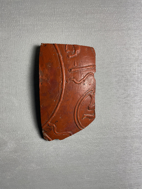 <em>Arretine Sherd</em>, 100 B.C.E.-100 C.E. Clay, slip, 2 5/16 × 9/16 × 4 1/16 in. (5.8 × 1.5 × 10.3 cm). Brooklyn Museum, By exchange, 00.58. Creative Commons-BY (Photo: Brooklyn Museum, CUR.00.58_view01.jpeg)