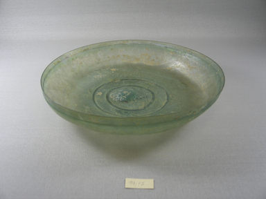 Roman. <em>Dish of Plain Blown Glass</em>, 4th-5th century C.E. Glass, 1 5/16 x Diam. 10 1/2 in. (3.4 x 26.6 cm). Brooklyn Museum, Gift of Robert B. Woodward, 01.13. Creative Commons-BY (Photo: Brooklyn Museum, CUR.01.13.jpg)