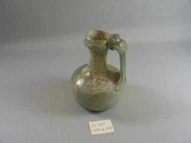 Roman. <em>Jug of Blown Green Glass</em>, 1st-5th century C.E. Glass, 5 3/16 x greatest diam. 3 3/8 in. (13.2 x 8.6 cm). Brooklyn Museum, Gift of Robert B. Woodward, 01.135. Creative Commons-BY (Photo: Brooklyn Museum, CUR.01.135_view1.jpg)