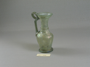 Roman. <em>Jug of Blown Glass</em>, 1st-5th century C.E. Glass, 4 7/16 x 1 3/4 x 2 11/16 in. (11.2 x 4.5 x 6.8 cm). Brooklyn Museum, Gift of Robert B. Woodward, 01.192. Creative Commons-BY (Photo: Brooklyn Museum, CUR.01.192_view1.jpg)