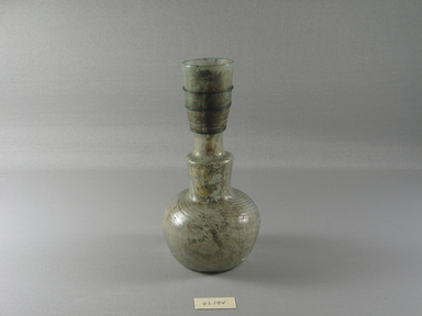 Roman. <em>Bottle of Blown Glass</em>, 4th-5th century C.E. Glass, 6 3/4 x Diam. 3 1/4 in. (17.2 x 8.3 cm). Brooklyn Museum, Gift of Robert B. Woodward, 01.194. Creative Commons-BY (Photo: Brooklyn Museum, CUR.01.194_view1.jpg)