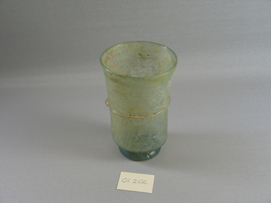 Roman. <em>Beaker</em>, 4th century C.E. Glass, 4 5/16 x greatest diam. 2 15/16 in. (11 x 7.4 cm) . Brooklyn Museum, Gift of Robert B. Woodward, 01.202. Creative Commons-BY (Photo: Brooklyn Museum, CUR.01.202.jpg)