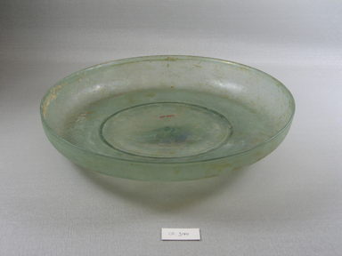 Roman. <em>Shallow Bowl of Molded Green Glass</em>, late 4th century C.E. Glass, 1 15/16 x Diam. 10 5/8 in. (5 x 27 cm)  . Brooklyn Museum, Gift of Robert B. Woodward, 01.390. Creative Commons-BY (Photo: Brooklyn Museum, CUR.01.390_view1.jpg)