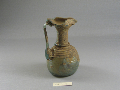 Roman. <em>Jug of Blown Glass</em>, 1st-5th century C.E. Glass, 2 13/16 x 4 5/8 in. (7.1 x 11.8 cm)  . Brooklyn Museum, Gift of Robert B. Woodward, 01.413. Creative Commons-BY (Photo: Brooklyn Museum, CUR.01.413_view2.jpg)