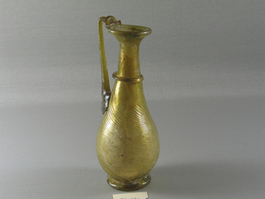 Roman. <em>Flask with Handle and Diagonal Ribs</em>, 3rd-4th century C.E. Glass, 6 5/8 x 2 1/2 in. (16.9 x 6.3 cm). Brooklyn Museum, Gift of Robert B. Woodward, 01.436. Creative Commons-BY (Photo: Brooklyn Museum, CUR.01.436_view3.jpg)
