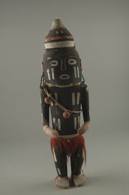 Hopi Pueblo. <em>Kachina Doll (Pookon)</em>, late 19th century. Wood, pigment, fiber cord, shell, 10 5/8 x 3 x 1 3/4 in. (27 x 7.6 x 4.4 cm). Brooklyn Museum, Museum Expedition 1904, Museum Collection Fund, 04.297.5560. Creative Commons-BY (Photo: Brooklyn Museum, CUR.04.297.5560_front.jpg)
