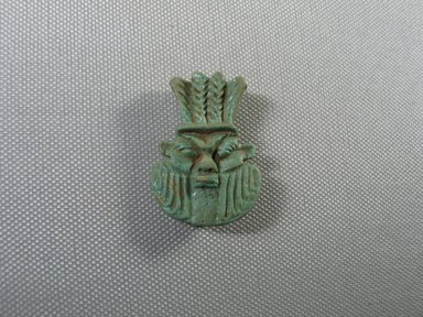 <em>Head of Bes Amulet</em>, ca. 760-656 B.C.E. Faience, 1 5/8 × 1 1/8 × 7/16 in. (4.1 × 2.9 × 1.1 cm). Brooklyn Museum, Charles Edwin Wilbour Fund, 05.344. Creative Commons-BY (Photo: , CUR.05.344_view01.jpg)