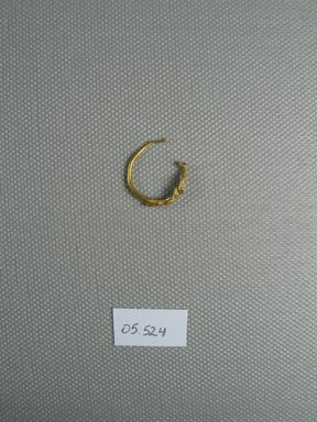 <em>Earring</em>, 2nd century B.C.E. Gold, Greatest Diam. 5/8 in. (1.6 cm). Brooklyn Museum, Ella C. Woodward Memorial Fund, 05.524. Creative Commons-BY (Photo: Brooklyn Museum, CUR.05.524_view1.jpg)