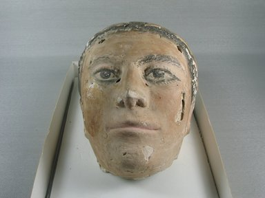 Graeco-Egyptian. <em>Mask of a Young Man</em>, late 1st century C.E. Plaster, pigment, 5 7/8 x 5 5/16 x 6 1/8 in. (15 x 13.5 x 15.5 cm). Brooklyn Museum, Museum Collection Fund, 06.284. Creative Commons-BY (Photo: Brooklyn Museum, CUR.06.284_view1.jpg)