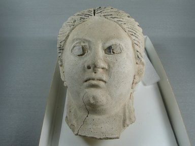 Graeco-Egyptian. <em>Mask of a Woman</em>, ca. 150 C.E.-175 C.E. Plaster, glass, 5 11/16 x 5 3/16 x 9 5/8 in. (14.5 x 13.2 x 24.5 cm). Brooklyn Museum, Museum Collection Fund, 06.286. Creative Commons-BY (Photo: Brooklyn Museum, CUR.06.286_view1.jpg)