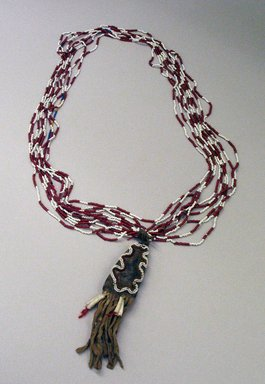 Plains. <em>Medicine Necklace with Pouch Containing Umbilical Cord</em>, late 19th or early 20th century. Bead, hide, shell, string, yarn, approx. 23 x 5 in. or (66 x 3.5 cm). Brooklyn Museum, Brooklyn Museum Collection, 08.433. Creative Commons-BY (Photo: Brooklyn Museum, CUR.08.433_view1.jpg)