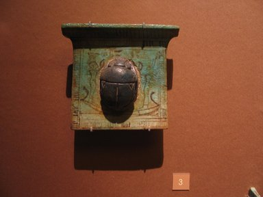 <em>Pectoral with Scarab</em>, ca. 1539-1295 B.C.E. or later. Faience, 4 1/16 x 3 11/16 x 3/8 in. (10.3 x 9.4 x 1 cm). Brooklyn Museum, Charles Edwin Wilbour Fund, 08.480.159. Creative Commons-BY (Photo: Brooklyn Museum, CUR.08.480.159_mummychamber.jpg)