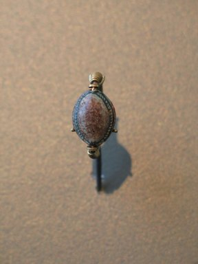 <em>Cowrie-Shaped Amulet in Gold Ring</em>, ca. 1630-1539 B.C.E. Steatite, glaze, gold, 9/16 x Diam. 15/16 in. (1.5 x 2.4 cm). Brooklyn Museum, Charles Edwin Wilbour Fund, 08.480.199. Creative Commons-BY (Photo: Brooklyn Museum, CUR.08.480.199_view1_erg2.jpg)