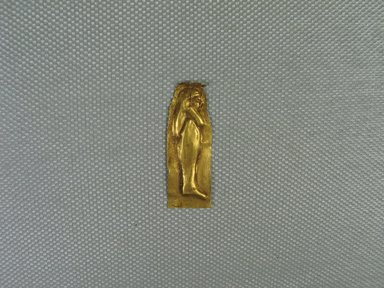 <em>Plaque - Standing Mummiform in Relief</em>, n.d. Gold, 1 5/16 x 1/2 x 1/16 in. (3.4 x 1.2 x 0.2 cm). Brooklyn Museum, Charles Edwin Wilbour Fund, 08.480.215. Creative Commons-BY (Photo: Brooklyn Museum, CUR.08.480.215_view1.jpg)