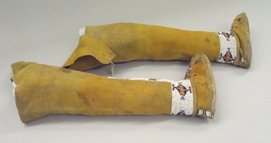 Osage. <em>Girl's Moccasins Attached to Leggings</em>, late 19th-early 20th century. Hide, pigment, beads, 20 1/2 x 7 7/8 in.  (52.0 x 20.0 cm). Brooklyn Museum, Museum Expedition 1911, Museum Collection Fund, 11.694.9002. Creative Commons-BY (Photo: Brooklyn Museum, CUR.11.694.9002a-b_view2.jpg)