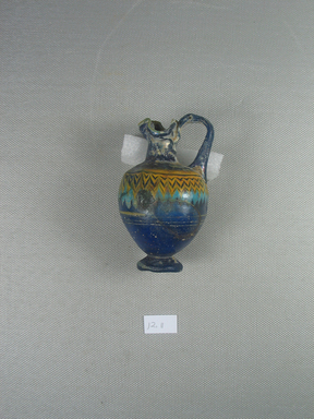 Greek. <em>Oinochoe</em>, late 6th-early 4th century B.C.E. Glass, 3 1/4 × Diam. 2 1/8 in. (8.3 × 5.4 cm). Brooklyn Museum, Purchased with funds given by Robert B. Woodward, 12.11. Creative Commons-BY (Photo: Brooklyn Museum, CUR.12.11_side_view2.jpg)