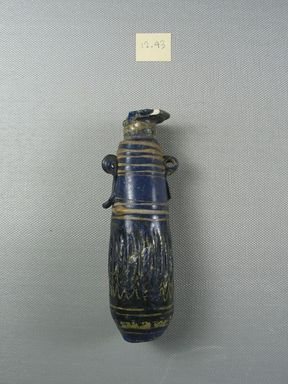<em>Cylindrical Alabastron</em>, late 6th-early 4th century B.C.E. Glass, 1 3/8 x 11/16 x 4 7/8 in. (3.5 x 1.8 x 12.4 cm). Brooklyn Museum, Purchased with funds given by Robert B. Woodward, 12.43. Creative Commons-BY (Photo: Brooklyn Museum, CUR.12.43_side.jpg)