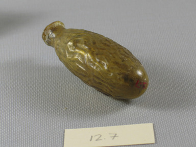 Roman. <em>Date-Shaped Bottle</em>, mid-1st to early 2nd century C.E. Glass, 3 x 1 1/16 in. (7.6 x 2.7 cm). Brooklyn Museum, Gift of Aziz Khayat, 12.7. Creative Commons-BY (Photo: Brooklyn Museum, CUR.12.7_view1.jpg)
