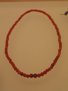 <em>Necklace</em>, ca. 1938-1700 B.C.E. Carnelian, 10 7/16 in. (26.5 cm). Brooklyn Museum, Gift of the Egypt Exploration Fund, 13.1026. Creative Commons-BY (Photo: Brooklyn Museum, CUR.13.1026_mummychamber.jpg)