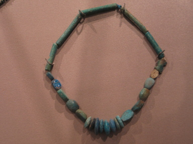<em>Single Strand Necklace with Bead and 5 Scarabs</em>, ca. 1390-1292 B.C.E. Faience, Overall Length: 12 5/8 in. (32 cm). Brooklyn Museum, Gift of the Egypt Exploration Fund, 15.498. Creative Commons-BY (Photo: Brooklyn Museum, CUR.15.498_erg456.jpg)