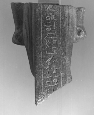 <em>Fragment of a Standing Statue</em>. Red quartzite, 6 7/16 x 5 5/16 in. (16.3 x 13.5 cm). Brooklyn Museum, Gift of Evangeline Wilbour Blashfield, Theodora Wilbour, and Victor Wilbour honoring the wishes of their mother, Charlotte Beebe Wilbour, as a memorial to their father, Charles Edwin Wilbour, 16.172. Creative Commons-BY (Photo: Brooklyn Museum, CUR.16.172_NegID_CEG690_print_cropped_bw.jpg)