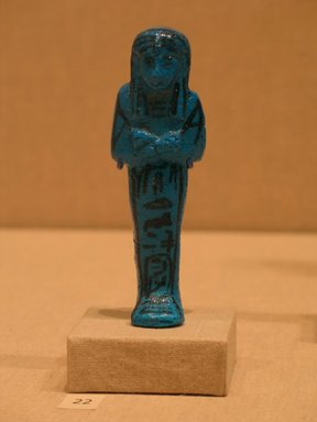 <em>Funerary Figurine of King Pinudjem I</em>, ca. 1025-1007 B.C.E. Faience, 4 5/16 × 1 3/8 × 1 in. (10.9 × 3.5 × 2.5 cm). Brooklyn Museum, Gift of Evangeline Wilbour Blashfield, Theodora Wilbour, and Victor Wilbour honoring the wishes of their mother, Charlotte Beebe Wilbour, as a memorial to their father, Charles Edwin Wilbour, 16.189. Creative Commons-BY (Photo: Brooklyn Museum, CUR.16.189_wwgA-3.jpg)