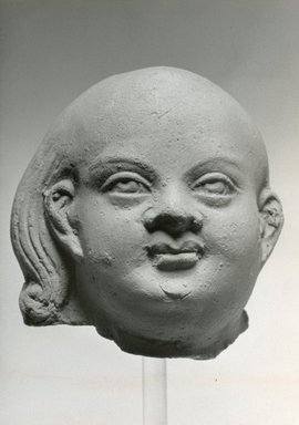 <em>Head of Harpocrates</em>, 2nd century C.E., or later. Terracotta, 2 5/8 x 2 11/16 x 2 3/4 in. (6.6 x 6.9 x 7 cm). Brooklyn Museum, Gift of Evangeline Wilbour Blashfield, Theodora Wilbour, and Victor Wilbour honoring the wishes of their mother, Charlotte Beebe Wilbour, as a memorial to their father, Charles Edwin Wilbour, 16.214. Creative Commons-BY (Photo: Brooklyn Museum, CUR.16.214_NegC_print_bw.jpg)