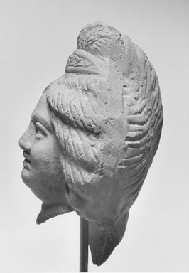<em>Head of Female</em>, 2nd-3rd century C.E. Clay, 4 3/16 x 2 5/8 x 2 7/16 in. (10.7 x 6.7 x 6.3 cm). Brooklyn Museum, Gift of Evangeline Wilbour Blashfield, Theodora Wilbour, and Victor Wilbour honoring the wishes of their mother, Charlotte Beebe Wilbour, as a memorial to their father, Charles Edwin Wilbour, 16.220. Creative Commons-BY (Photo: Brooklyn Museum, CUR.16.220_NegD_print_bw.jpg)