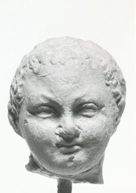 Graeco-Egyptian. <em>Head of Eros (?)</em>. Terracotta, 13/16 x 5/8 x 13/16 in. (2.1 x 1.6 x 2 cm). Brooklyn Museum, Gift of Evangeline Wilbour Blashfield, Theodora Wilbour, and Victor Wilbour honoring the wishes of their mother, Charlotte Beebe Wilbour, as a memorial to their father, Charles Edwin Wilbour, 16.229. Creative Commons-BY (Photo: Brooklyn Museum, CUR.16.229_NegA_print_bw.jpg)
