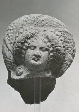 <em>Female Head</em>, 2nd-3rd century C.E. Clay, 3 7/16 x 2 5/8 x 2 3/16 in. (8.7 x 6.7 x 5.5 cm). Brooklyn Museum, Gift of Evangeline Wilbour Blashfield, Theodora Wilbour, and Victor Wilbour honoring the wishes of their mother, Charlotte Beebe Wilbour, as a memorial to their father, Charles Edwin Wilbour, 16.279. Creative Commons-BY (Photo: Brooklyn Museum, CUR.16.279_NegA_print_bw.jpg)