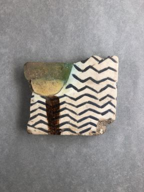 <em>Fragment of Tile with Water Scene</em>, ca. 1352-1332 B.C.E. Faience, 2 3/4 × 1/2 × 3 1/4 in. (7 × 1.2 × 8.2 cm). Brooklyn Museum, Gift of Evangeline Wilbour Blashfield, Theodora Wilbour, and Victor Wilbour honoring the wishes of their mother, Charlotte Beebe Wilbour, as a memorial to their father, Charles Edwin Wilbour, 16.335. Creative Commons-BY (Photo: Brooklyn Museum, CUR.16.335_view01.jpg)
