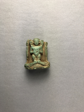 <em>Pataikos Flanked by Goddesses Amulet</em>, 664-30 B.C.E. Faience, 1 × 7/8 × 9/16 in. (2.5 × 2.2 × 1.5 cm). Brooklyn Museum, Gift of Evangeline Wilbour Blashfield, Theodora Wilbour, and Victor Wilbour honoring the wishes of their mother, Charlotte Beebe Wilbour, as a memorial to their father, Charles Edwin Wilbour, 16.398. Creative Commons-BY (Photo: , CUR.16.398_view01.jpg)